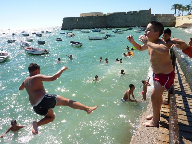 Children jump into the ocean near the Castillo de Santa Catalina in Cadiz, Spain, July 2014.