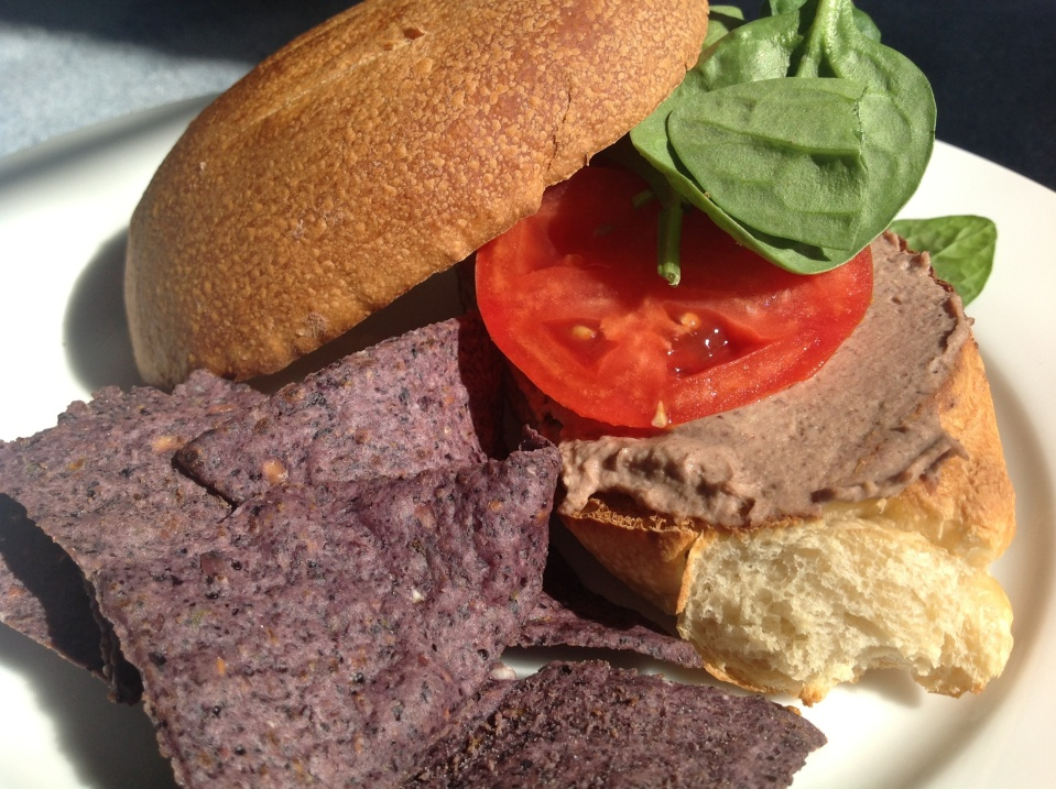 Black bean green chile hummus spread on a toasted bun and paired with homegrown tomatoes, spinach and blue corn chips.
